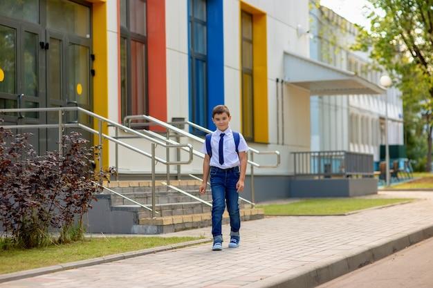 Scolaro felice in camicia bianca, cravatta blu e zaino lasciò la scuola con finestre multicolori