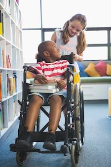 Scolaro di trasporto scolara felice in sedia a rotelle
