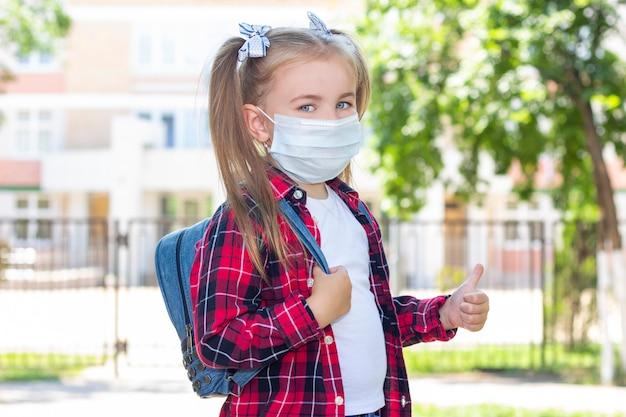 La studentessa felice in una maschera protettiva con uno zaino mostra come. in una maglietta bianca e una camicia a quadri