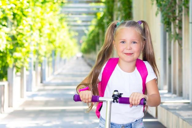 Scolara felice su uno scooter con uno zaino.