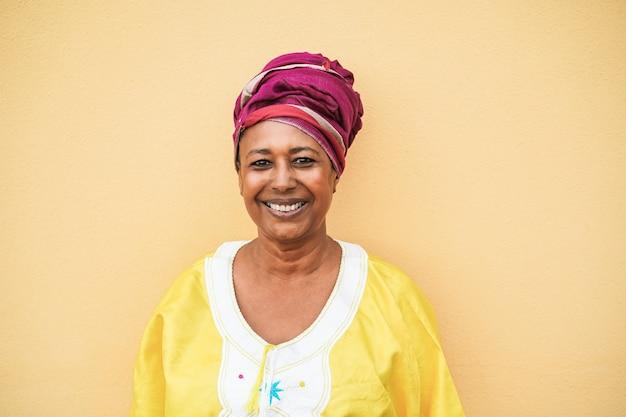 Felice donna africana anziana che indossa abiti tradizionali guardando la telecamera - focus sul viso