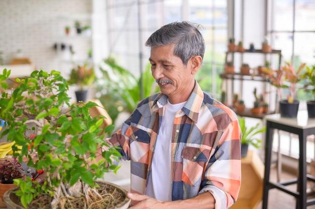 L'uomo in pensione asiatico senior felice sta rilassando e godendo l'attività di svago in giardino a casa.