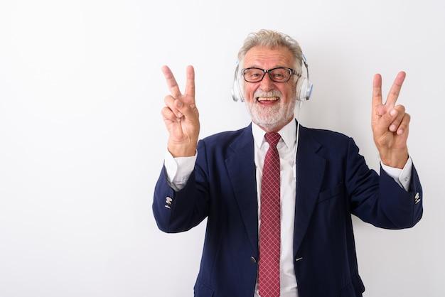 Felice senior barbuto imprenditore sorridente e dando segno di pace con entrambe le mani mentre si ascolta la musica su bianco