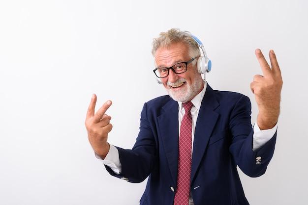 Felice senior barbuto imprenditore sorridente e in posa con segni di pace mentre si ascolta la musica su bianco