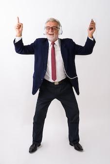 Uomo d'affari barbuto senior felice che sorride mentre balla e ascolta la musica su bianco