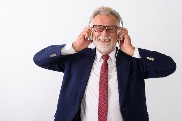 Felice senior barbuto imprenditore sorridente durante l'ascolto di musica e tenendo le cuffie su bianco