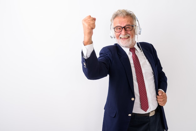 Felice senior barbuto imprenditore sorridente mentre si ascolta la musica e guardando motivato con gli occhiali su bianco