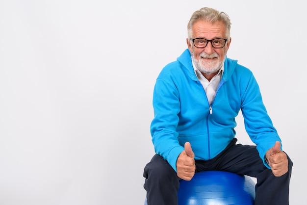 Uomo barbuto senior felice che sorride e che dà i pollici in su mentre si siede sulla palla della palestra pronta per la palestra su bianco