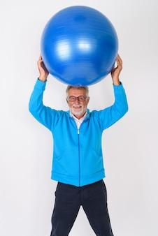 Felice senior barbuto uomo sorridente e in piedi mentre si tiene la palla da ginnastica in cima alla testa pronta per la palestra su bianco