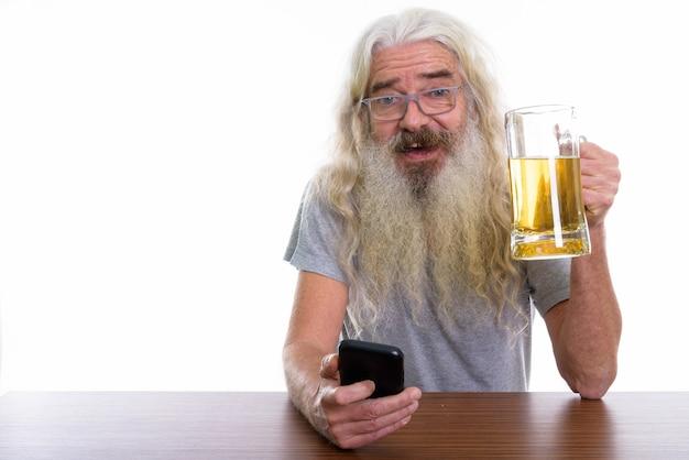 Felice senior barbuto uomo sorridente mentre si tiene un barattolo di birra