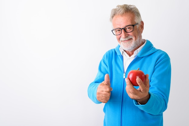 Uomo barbuto senior felice che sorride mentre tiene mela rossa e che dà pollice in su pronto per la palestra su bianco