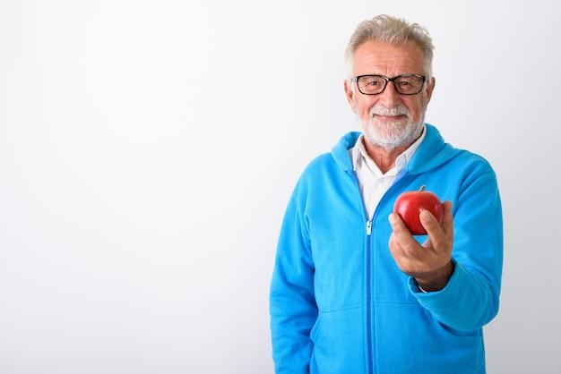 Felice senior barbuto uomo sorridente mentre si tiene la mela rossa pronta per la palestra su bianco