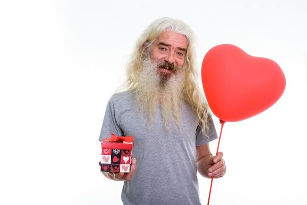 Uomo barbuto senior felice che sorride mentre tiene cuore rosso