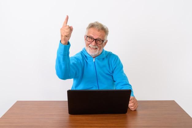 Felice senior barbuto uomo sorridente mentre punta il dito verso l'alto mentre è seduto con il computer portatile sul tavolo di legno su bianco