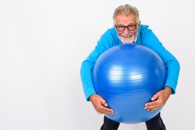 Felice senior barbuto uomo sorridente in piedi e tenendo palla palestra pronto per la palestra su bianco