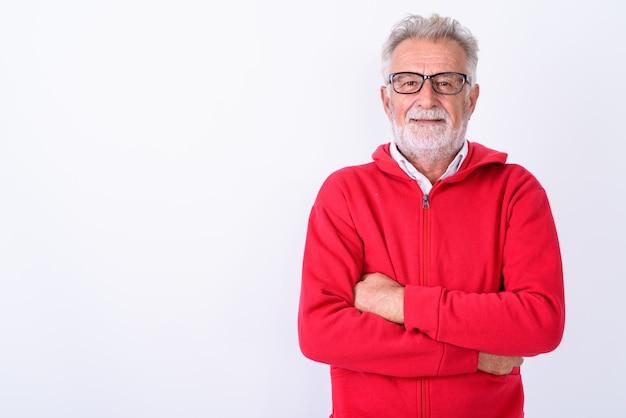 Felice uomo barbuto senior sorridente con le braccia incrociate su bianco