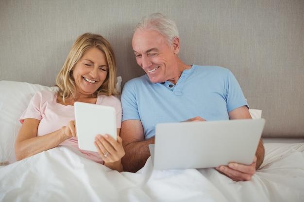 Felice coppia senior sul letto utilizzando laptop e tablet digitale