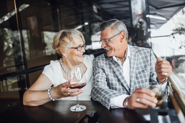 Felice coppia senior tintinnio di bicchieri di vino bianco, celebrando l'anniversario