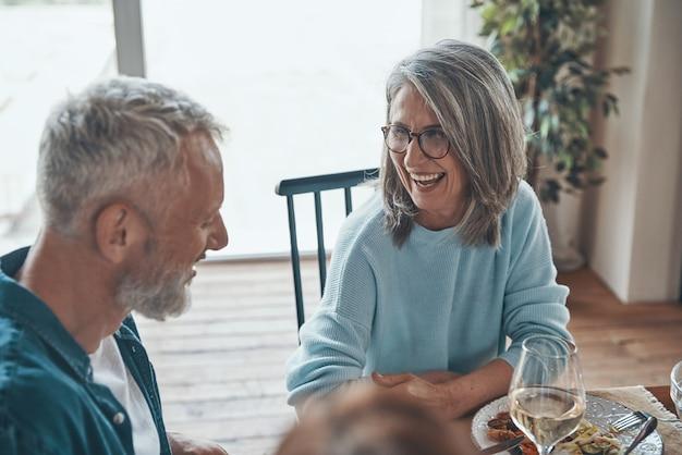 Felice coppia senior che comunica e sorride mentre cena insieme