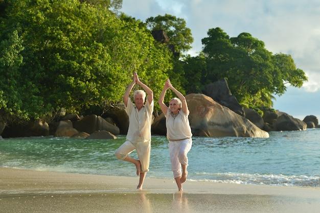 Felice coppia senior che fa yoga che si esercita in estate in riva al mare