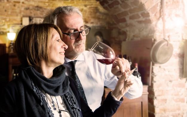 Coppie senior felici che bevono un bicchiere di vino Foto Premium