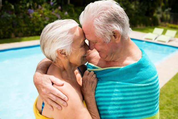Coppie maggiori felici che si abbracciano a bordo piscina