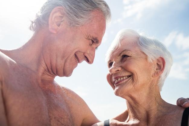 Felice coppia senior abbracciando faccia a faccia sulla spiaggia