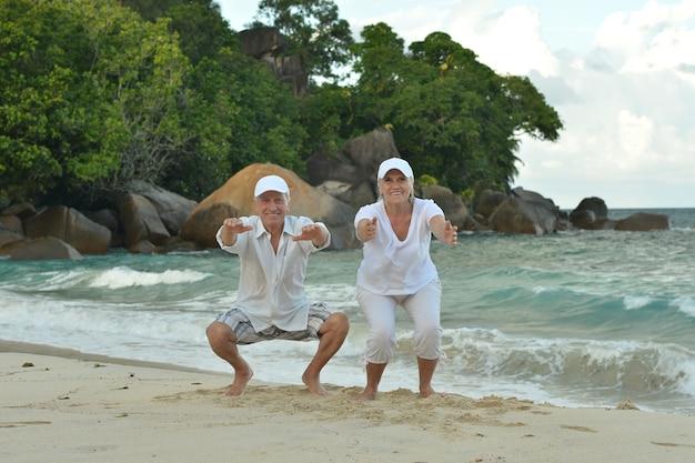 Felice coppia senior che si esercita in estate in riva al mare