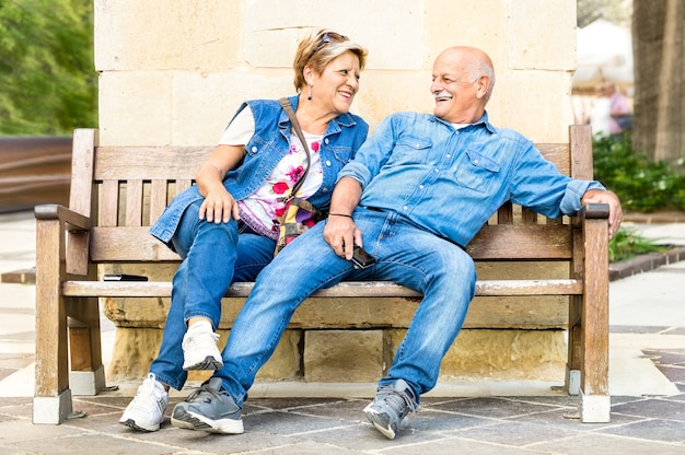 Felice coppia senior divertendosi su una panchina - concetto di anziani giocosi attivi durante il pensionamento - stile di vita quotidiano nel pomeriggio soleggiato autunnale