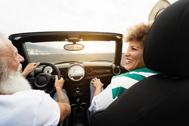 Felice coppia senior divertendosi in autovettura convertibile durante le vacanze estive - focus sul volto di donna