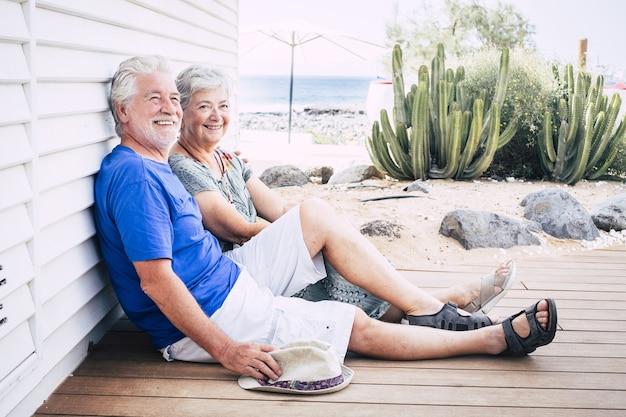 Felice coppia anziana che ride seduta per terra su assi di legno in una giornata estiva