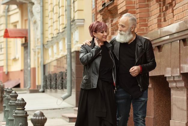 Coppie senior felici nell'amore durante la pensione. stile di vita anziano allegro con l'uomo che bisbiglia e che sorride con sua moglie.