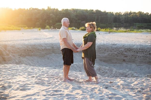 Coppie senior felici nell'amore fuori in spiaggia in natura di estate