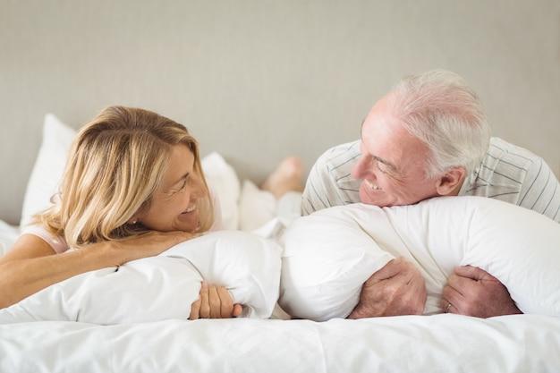 Coppie senior felici che si trovano sul letto