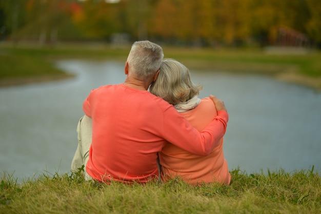 Felice coppia senior vicino al lago durante il tramonto in autunno