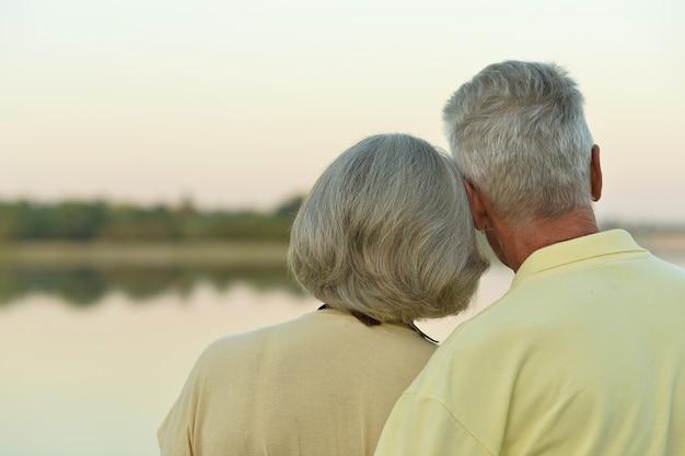 Felice coppia senior vicino al lago durante il tramonto in estate