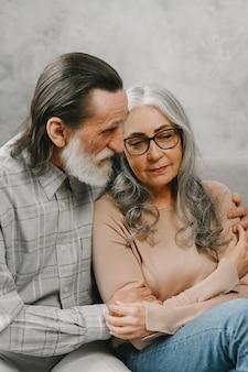 Felice coppia senior seduta sul divano a casa e parlando. concetto di tempo di qualità.