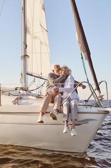 Felice coppia senior seduta sul lato della barca a vela o sul ponte dello yacht che galleggia nel bacio dell'uomo del mare