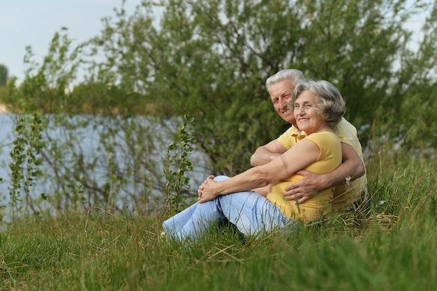 Felice coppia senior seduta in estate vicino al lago durante il tramonto, vista posteriore