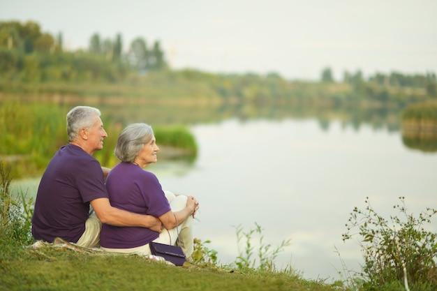 Felice coppia senior seduta in estate vicino al lago durante il tramonto