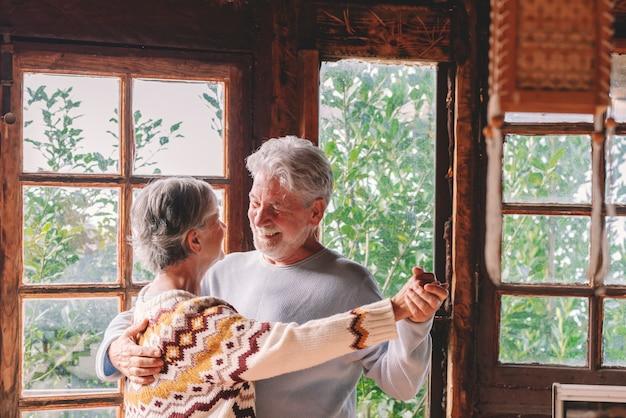 Felice coppia senior sorride e balla a casa godendosi l'amore e la relazione insieme. il vecchio e la donna attivi si divertono nell'attività di svago al coperto. la natura dei boschi vista dalle finestre