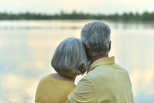Felice coppia senior in estate vicino al lago durante il tramonto, vista posteriore
