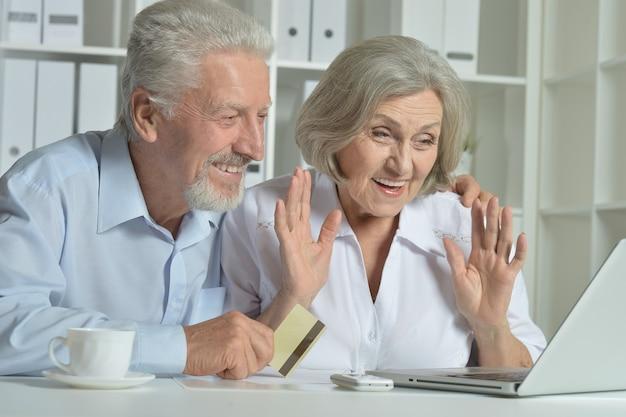 Felice coppia senior con laptop e biglietto da visita a casa