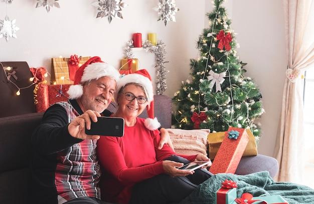 Felice coppia senior con cappelli di babbo natale che si gode dispositivi tecnologici con albero di natale e regali per la famiglia sullo sfondo. amore e concetto di famiglia