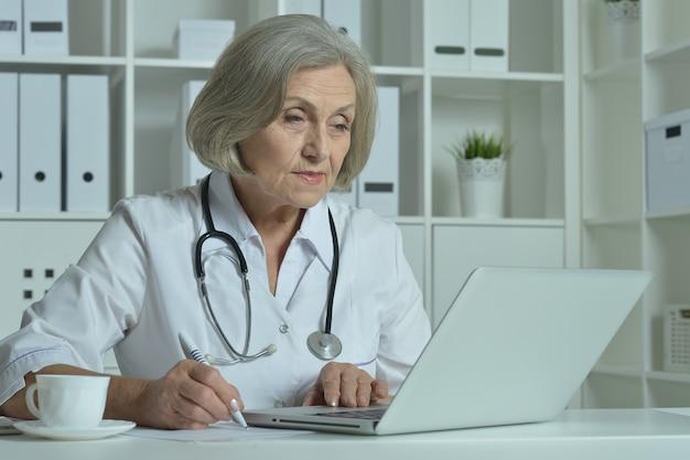 Felice medico senior seduto al tavolo con il computer portatile in ufficio