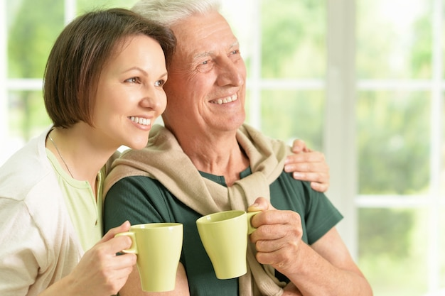 Felice padre anziano con la figlia a casa con il tè