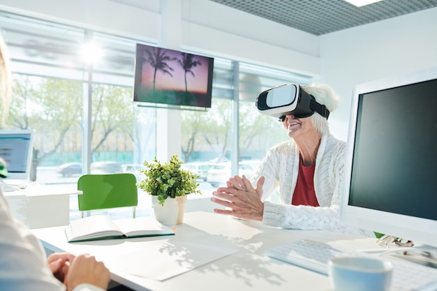 Signora senior felice nel simulatore di vr che gode del giro virtuale
