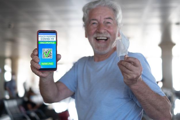 Felice uomo anziano in aeroporto in attesa di imbarco mostra passaporto verde sul telefono cellulare per le persone vaccinate di covid-19, togliendosi la maschera protettiva