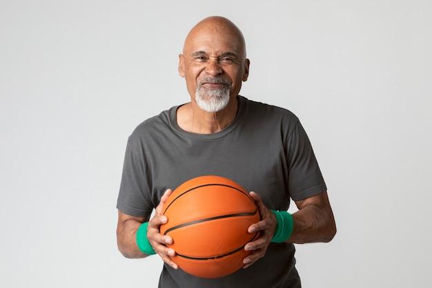Uomo anziano felice che tiene un basketba