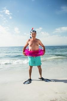 Felice l'uomo maggiore in anello gonfiabile e pinne in piedi sulla spiaggia